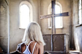 Girl sitting in front of the church cross. — Stock Photo
