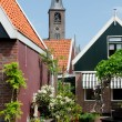 Old wooden house and church at Volendam - Stock Photo