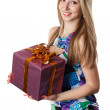 Young Woman holding a gift isolated on a white background — Stock Photo