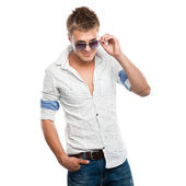 Fashion shot of an elegant young man in sunglasses — Stock Photo