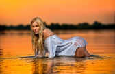 Sexy blonde woman in water at sunset .Beautiful swimsuit model in the water — Stock Photo