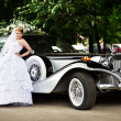 Luxury bride in a wedding dress about retro limousine — Stock Photo #10804550