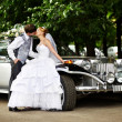 Groom adn bride about retro limousine — Stock Photo