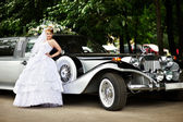 Luxury bride in a wedding dress about retro limousine — Stock Photo