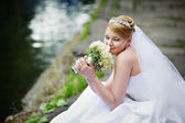 Happy bride in wedding dress with bouquet — Stock Photo