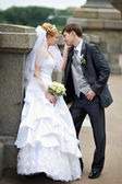 Happy bride and groom at wedding walk on bridge — Stock Photo