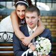 Stock Photo: Happy bride and groom on park bench