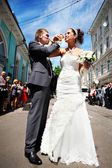 Happy bride and groom at wedding walk in street — Stock Photo