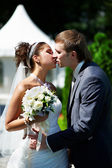 Kiss happy bride and groom at wedding walk in park — Stock Photo