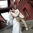 Happy bride and groom on the background of the old red building — Stock Photo