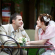 Happy bride and groom sit at table in cafe — Stock Photo #10830792