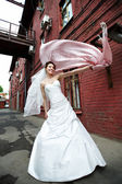 Happy bride on the background of the old red building — Stock Photo