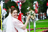 Elegant Bride at metal installation in park — Stock Photo