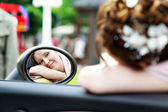 Happy bride looks in mirror of car at wedding walk — Stock Photo
