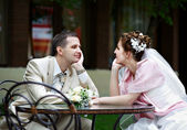 Happy bride and groom sit at table in cafe — Stock Photo