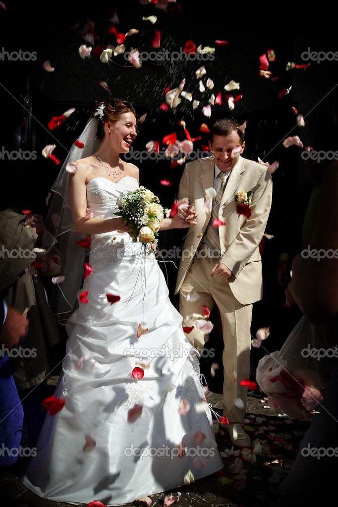 Happy marriage with rose petals. The bride and groom emerge from registrar. — Stock Photo #10831521