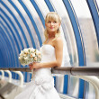 Happy bride with wedding bouquet on bridge — Stock Photo