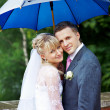 Happy bride and groom at wedding under an umbrella — Stock Photo
