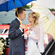 Happy bride and groom at wedding walk around red limousine — Stock Photo