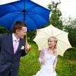 Happy bride and groom at wedding walk with umbrellas in rain — Stock Photo