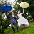 Happy bride and groom at wedding walk with umbrellas in rain — Stock Photo