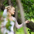 Beautiful bride in wedding dress stands near tree in park — Stock Photo