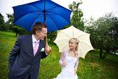 Gelukkige bruid en bruidegom op wedding lopen met paraplu's in regen — Stockfoto
