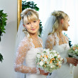 Stock Photo: Happy bride about mirrors in wedding palace