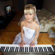 Beautiful Bride plays on electronic piano — Stock Photo