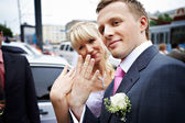 Happy bride and groom with wedding rings on hands — Stock Photo