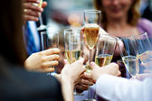 Glasses of champagne in hands of guests at wedding — Stock Photo