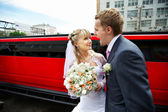 Humorous picture bride and groom on red limo — Zdjęcie stockowe
