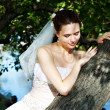 Beautiful bride in wedding dress stands near tree in park — Stock Photo #10885540
