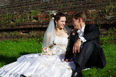 Happy bride and groom sit on the grass — Stock Photo