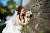 Russian bride with wedding bouquet near old castle — Stock Photo