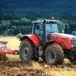Stock Photo: Tractor collecting haystack in field