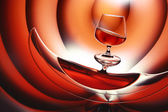 Glass of brandy and reflection on blue — Stock Photo