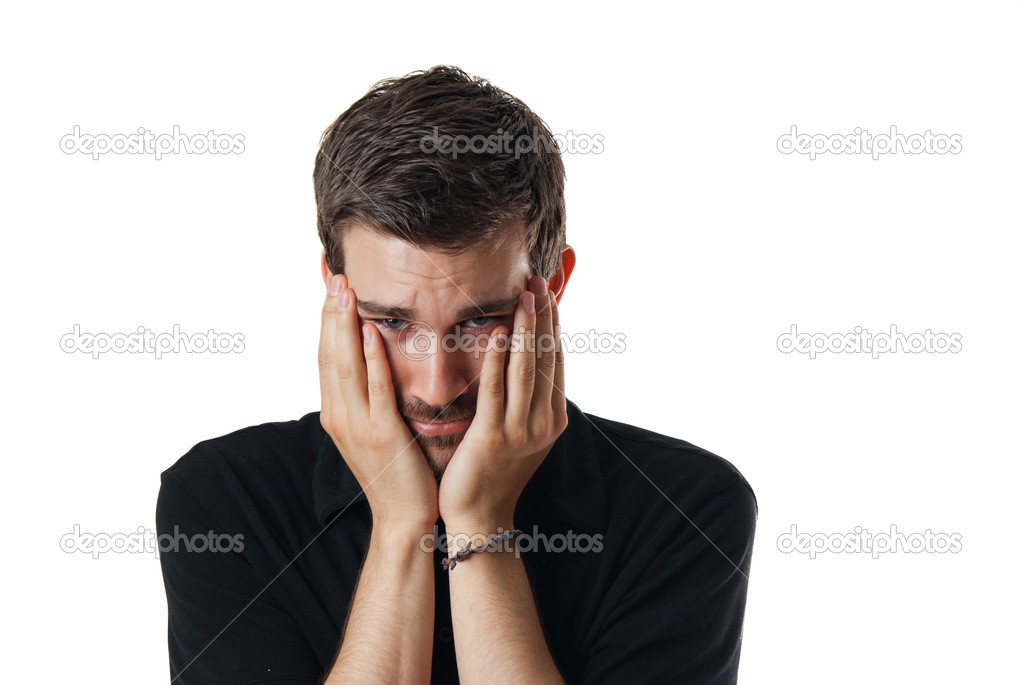 Upset worried young man with his face clasped in his hands and head bowed isolated on white — Stock Photo #10739758