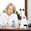 Female doctor in office writing — Stock Photo