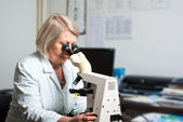 Healthcare researcher looking through a microscope — Stock Photo