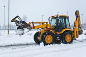 Yellow snow plow cleaning a road — Stock Photo