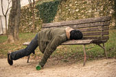 Drunk beggar sleeping on a bench with a bottle in hand — Stock Photo