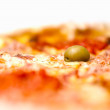 Pizza in extremely shallow depth of field with focus on olive - Stock Photo
