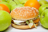 Chicken burger next to many apples and oranges — Stock Photo