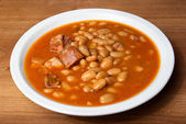 Baked beans in a plate on a wooden table — Stock Photo