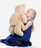 The lovely girl kisses the bear — Stock Photo