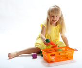 The girl puts toys in the container — Stockfoto
