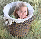 The girl hid in a wattled basket — Stock Photo