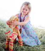 The girl plays in hay plays with a wattled goat — Stock fotografie