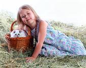 Dziewczyna na siano żelaza ulubionych królik w koszu siedzi — Zdjęcie stockowe